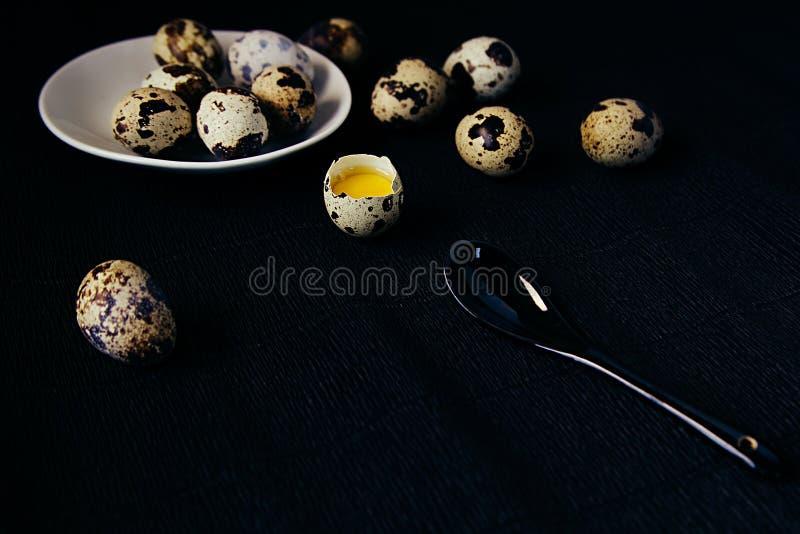 Яичка триперсток на черной текстурированной предпосылке Сырцовое сломанное яичко с желтком карточка пасха Взгляд со стороны стоковые изображения