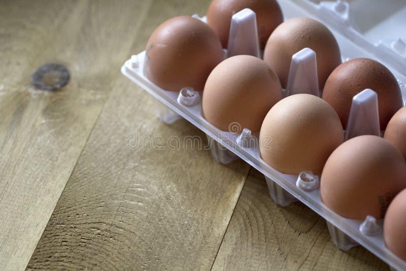 Яичка цыпленка Брайна сырцовые в пакете для яичек на коричневой таблице стоковые фотографии rf
