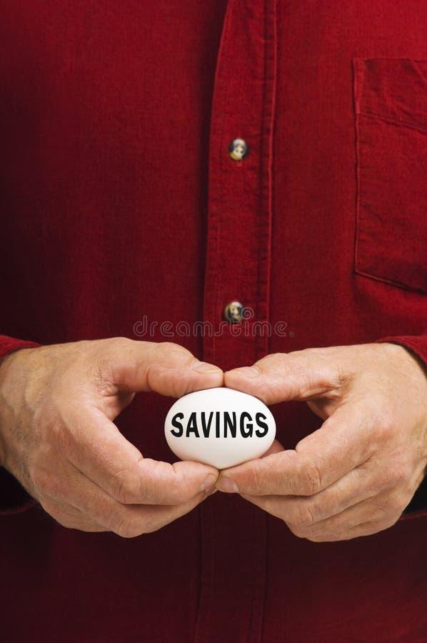 яичко держало сбережения человека написано стоковые изображения rf