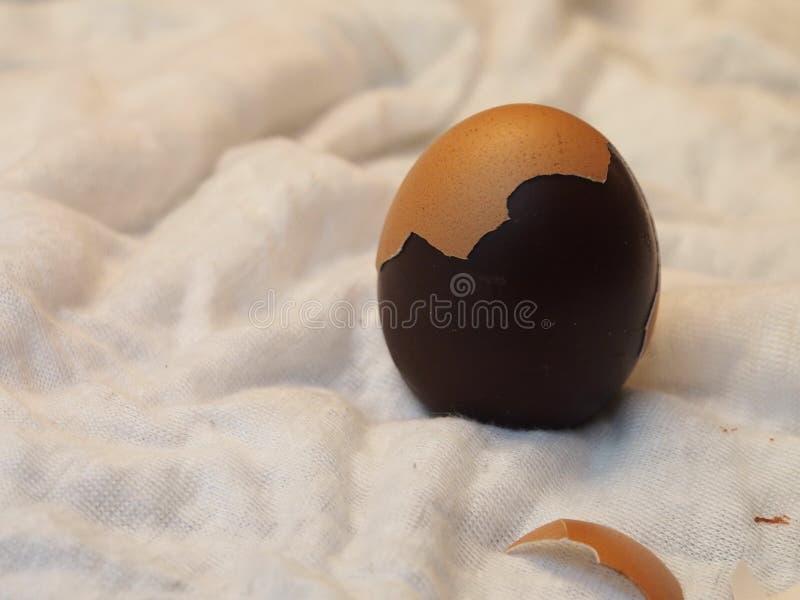 Яичко шоколада, частично раковина яичка, белая ткань стоковая фотография