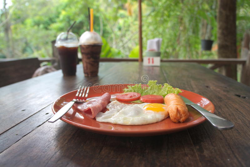 Яичница завтрака с ветчиной и горячей сосиской в плите на таблице стоковое фото rf