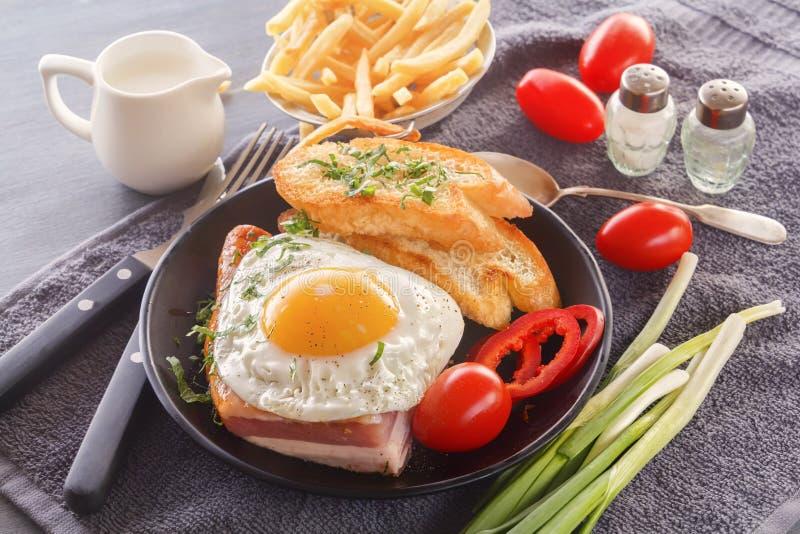 Яичница с беконом в черной плите с зажаренными кусками хлеба, томатами зеленых цветов, кувшином молока и французским картофелем ф стоковая фотография rf