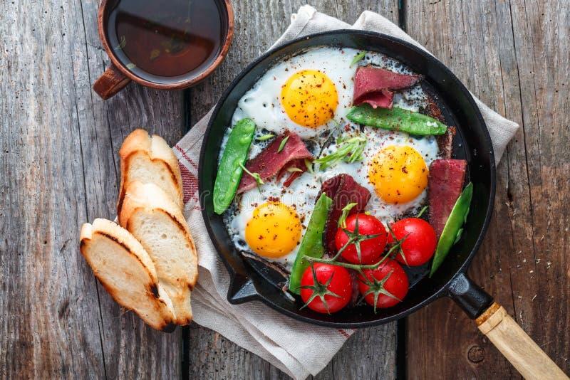 Яичницы в сковороде с томатами вишни, зелеными горохами и пастромой Copyspace стоковые фотографии rf