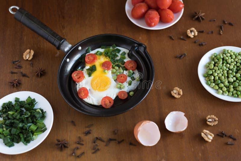 Яичницы с томатами и зелеными горохами стоковые изображения