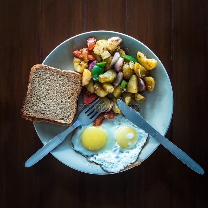 Яичницы с vegetable тушёным мясом и кудрявыми здравицами в плите стоковая фотография