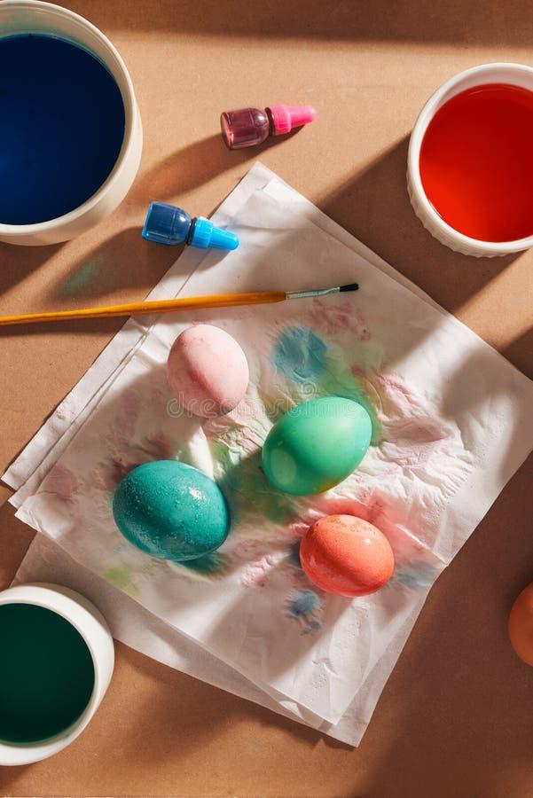 Яйца, красочные краски, щетки, карандаши на деревянной предпосылке, крася яйца, подготавливая для пасхи, праздник весны сезонный стоковое изображение rf