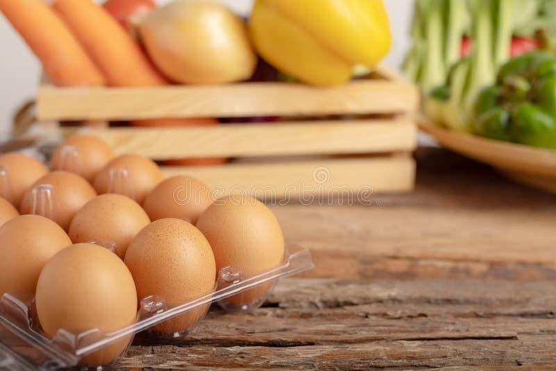 яйца на деревянном столе и овоще в деревянной коробке стоковая фотография rf