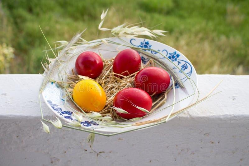 Яйца пасхи красные и желтые с сеном в плите снаружи стоковая фотография rf