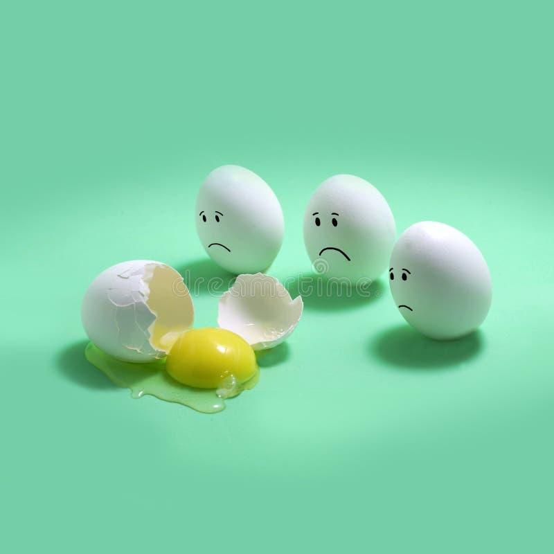 3 яйца с грустными сторонами рядом со сломленным яйцом стоковое фото