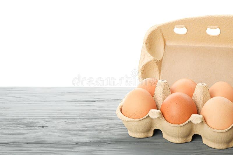 Яйца цыпленка Брауна в коробке коробки на деревянном столе изолированном на белой предпосылке стоковые изображения rf