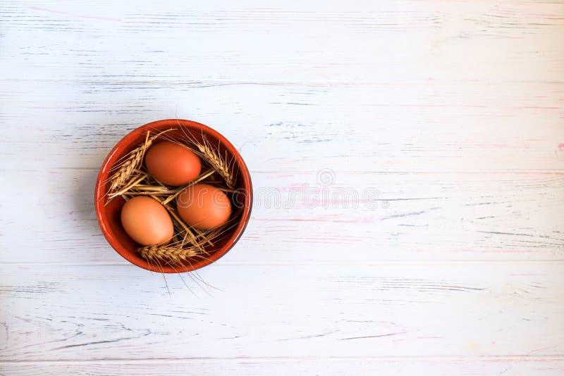 Яйца цыпленка Брауна органические в керамической круглой плите с ушами пшеницы на светлой деревянной предпосылке, концепции празд стоковые изображения rf