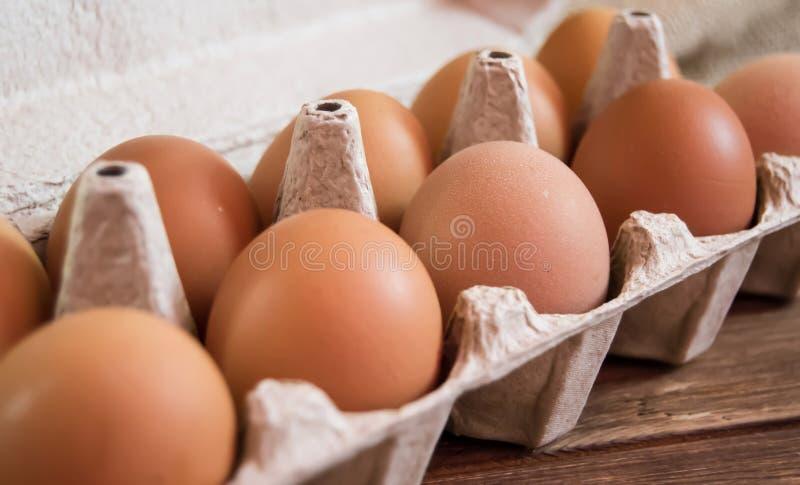Яйца цыпленка в пакете на деревянной предпосылке стоковые изображения