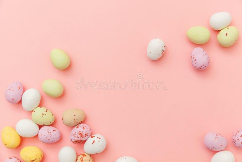 r Яйца шоколада конфеты пасхи и помадки мармелад-горошка изолированные на ультрамодной пастельной розовой предпосылке r стоковые фото