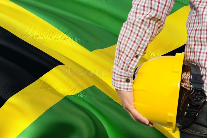 Ямайский инженер держит желтый шлем безопасности с развевать предпосылка флага Ямайки Концепция конструкции и здания стоковые изображения rf