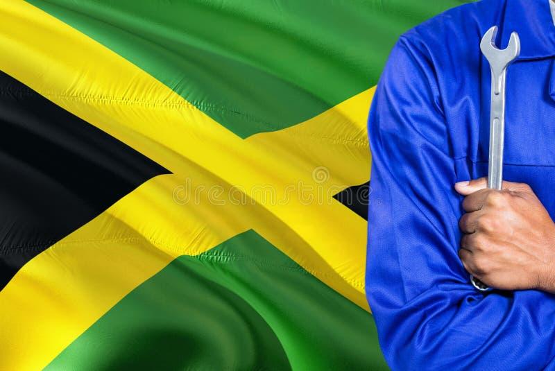 Ямайский механик в голубой форме держит ключ против развевать предпосылка флага Ямайки Пересеченный техник оружий стоковое фото rf