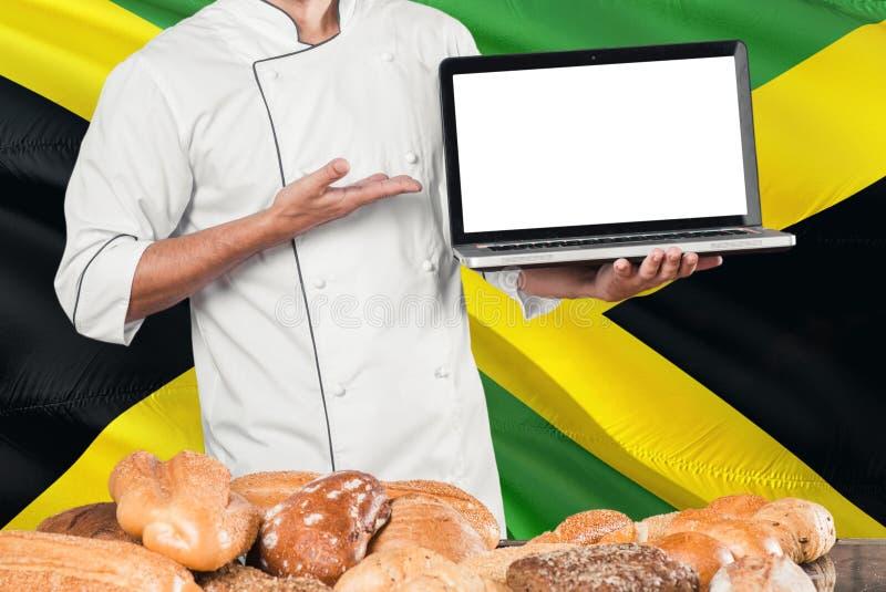 Ямайский ноутбук удерживания хлебопека на флаге Ямайки и предпосылке хлебов Форма шеф-повара нося указывая пустой экран для космо стоковое фото rf
