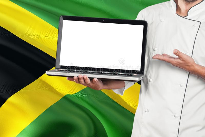 Ямайский ноутбук удерживания шеф-повара с пустым экраном на предпосылке флага Ямайки Сварите нося форму и ноутбук указывать для к стоковые фото