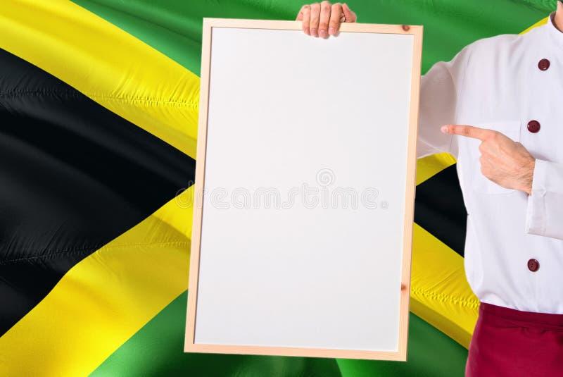 Ямайский шеф-повар держа пустое меню whiteboard на предпосылке флага Ямайки Сварите нося форму указывая космос для текста стоковые фото