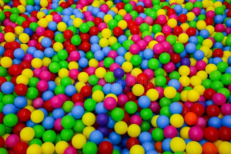 Яма шарика с красочными пластиковыми шариками в развлекательном центре детей Бассейн с яркой предпосылкой шариков Потеха, игра, и стоковое изображение