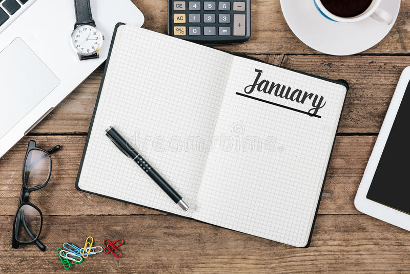 Январь, английское имя -го месяца на бумажном блокноте на столе офиса стоковое изображение rf