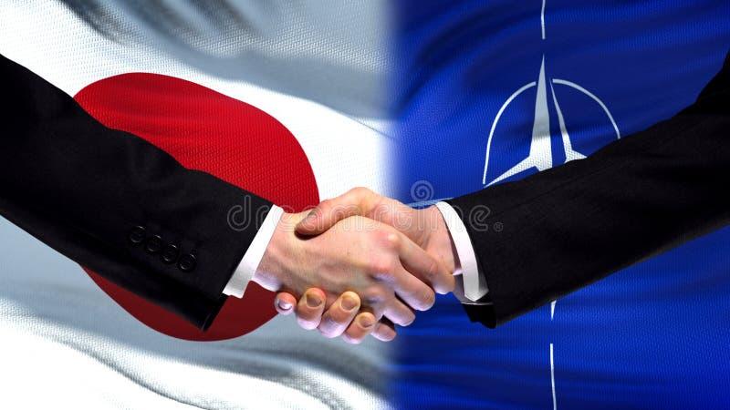 Япония и рукопожатие НАТО, международные отношения приятельства, предпосылка флага стоковое фото rf