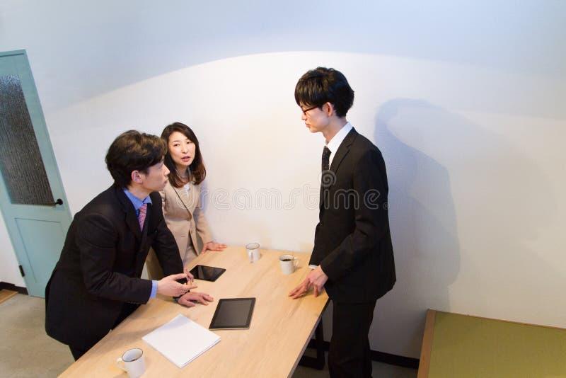 Японская встреча команды на столе, смотря документы на приборе таблетки стоковые фотографии rf