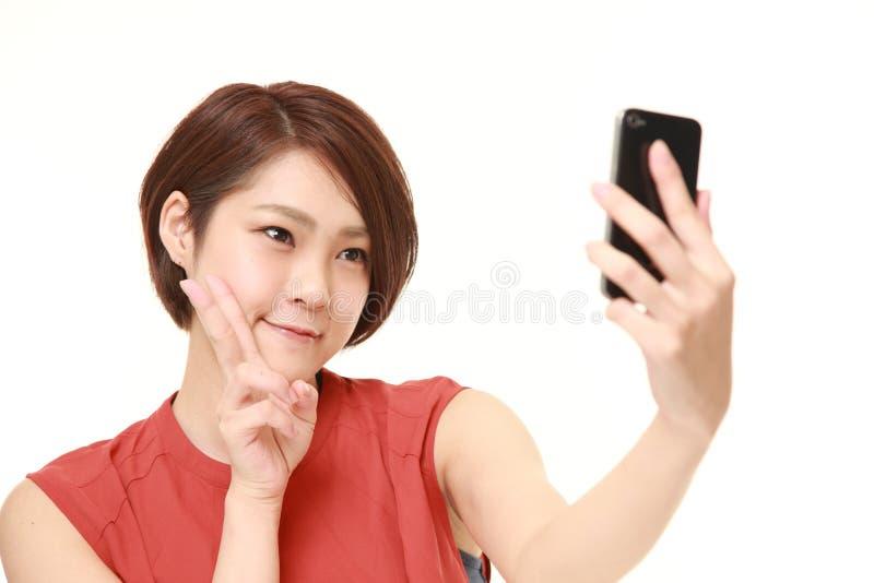 Японская женщина принимает selfie стоковое изображение