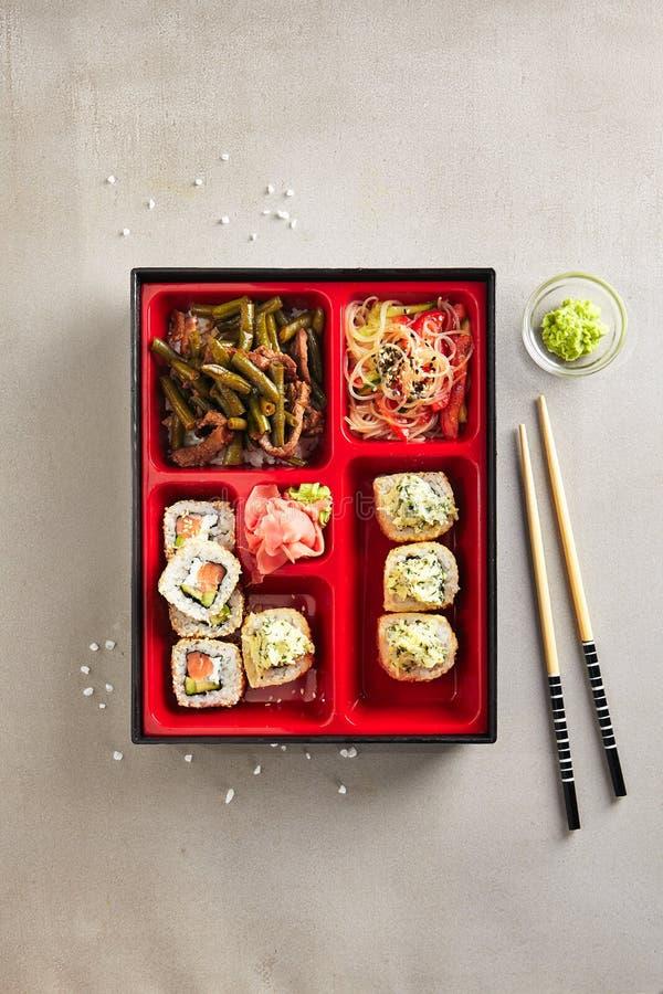 Японская коробка бенто с сушами Rolls, салатом и основным блюдом верхним v стоковые фотографии rf