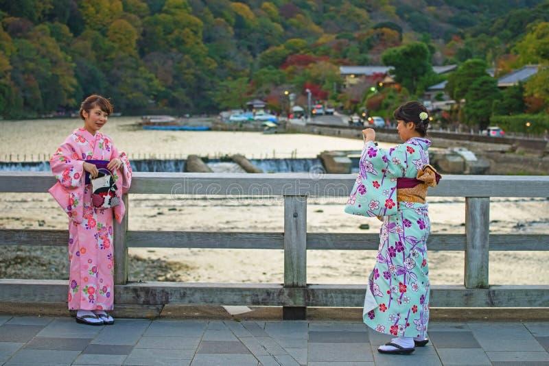 Японские девушки принимая фото на мост Togetsukyo стоковая фотография