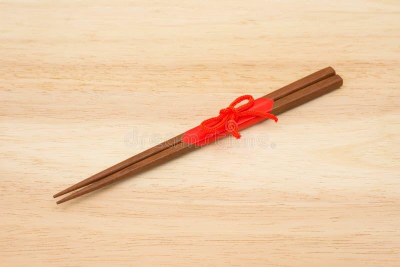 Японские деревянные палочки обернутые в красной бумаге и красной веревочке дальше стоковые изображения