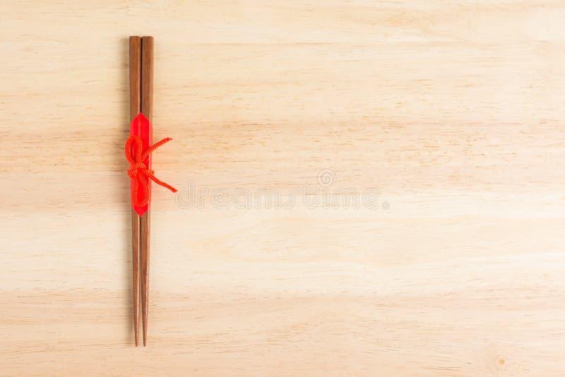 Японские деревянные палочки обернутые в красной бумаге и красной веревочке дальше стоковые изображения rf