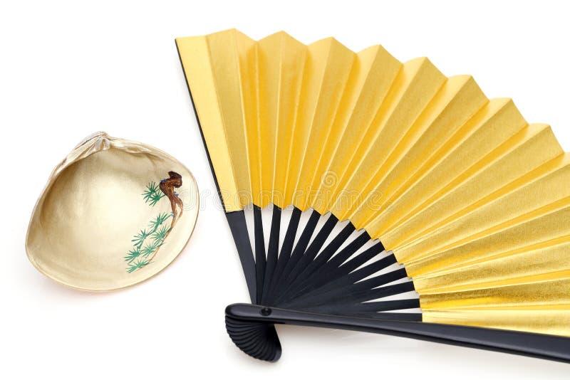Японские золотые складывая вентилятор и seashell стоковые изображения rf