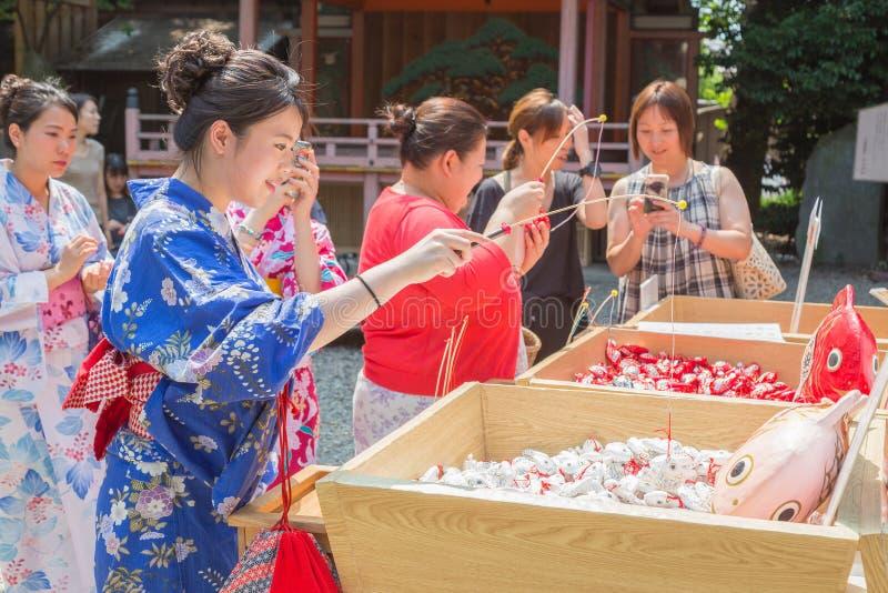 Японские и азиатские туристы пробуют их везение путем затравливать удачливый для стоковая фотография