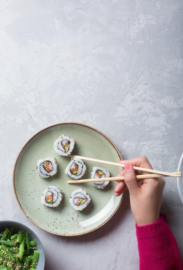 Японские суши и зеленые фасоли на белой предпосылке стоковые фото