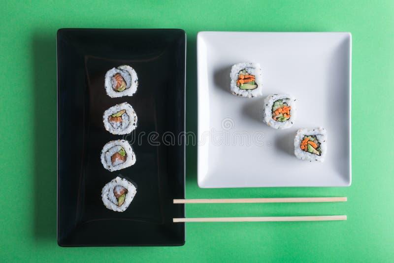 Японские суши на зеленой предпосылке Rolls и палочки стоковое фото