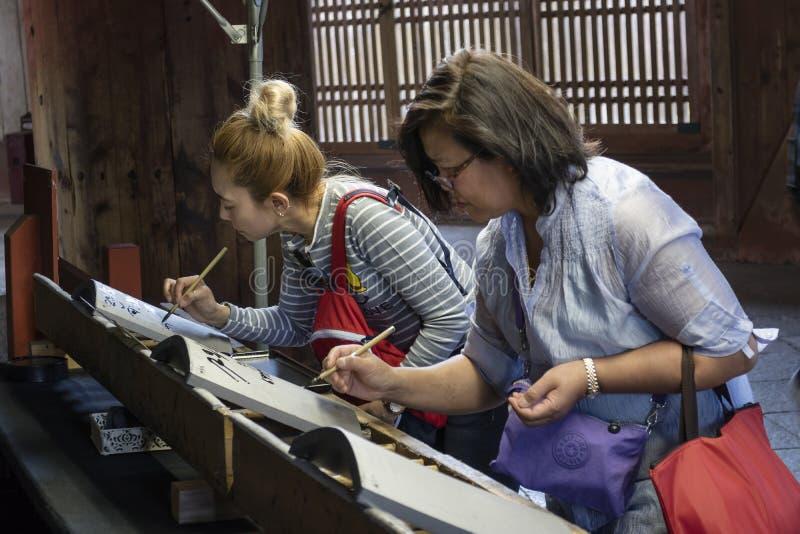 Японские туристы поддерживают обслуживание буддийского виска Todai-ji путем покупать и рисовать на черепице стоковое фото rf