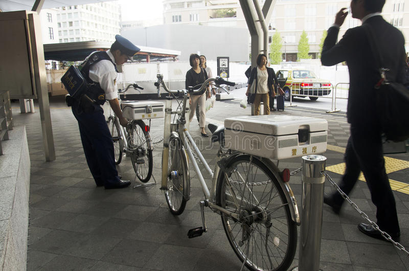 Японские люди полицейскиев останавливая велосипед после велосипеда bicycles c стоковые изображения