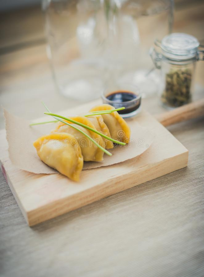 Японские guiozas с соусом сои на деревянной прерывая таблице стоковое фото