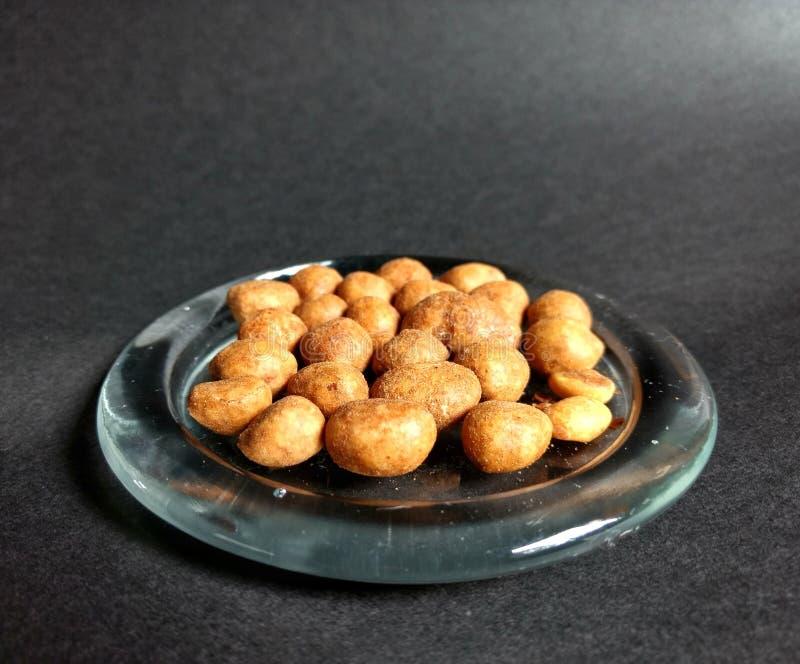 Японский арахис, который служат в стеклянном блюде с черной предпосылкой стоковые фотографии rf