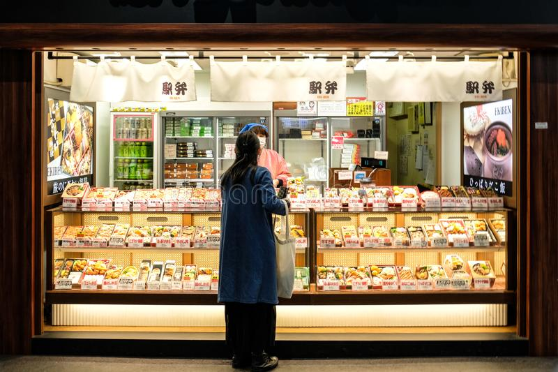 Японский клиент покупает коробку риса бенто на вокзале Киото стоковое изображение rf