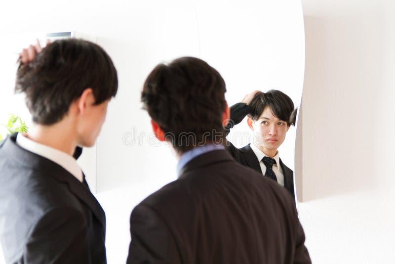 Японский молодой бизнесмен фиксируя вверх на зеркале с другом стоковые фотографии rf