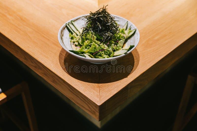 Японский салат огурцов с салатом из салата, радужной и сухой морской водорослей подан в керамическую чашу на деревянном прилавке стоковое фото rf