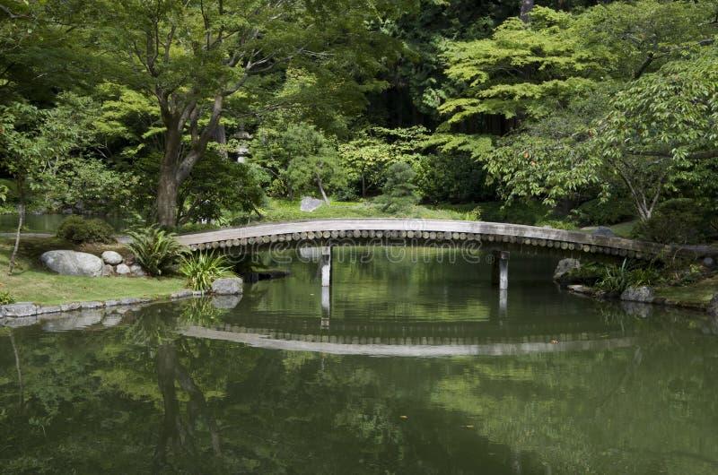 Японский сад с прудом и мостом стоковые изображения rf