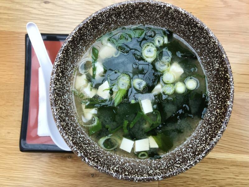 Японский суп мисо в коричневом шаре с белой ложкой на деревянном столе, горизонтальный взгляд сверху стоковые фото