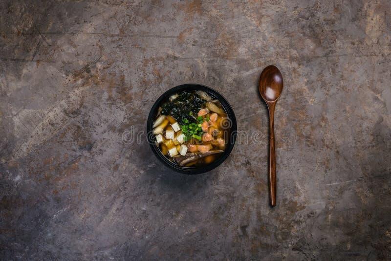 Японский суп мисо с тофу и семгами в черном шаре на годе сбора винограда покрасил предпосылку с деревянной ложкой Взгляд сверху стоковая фотография