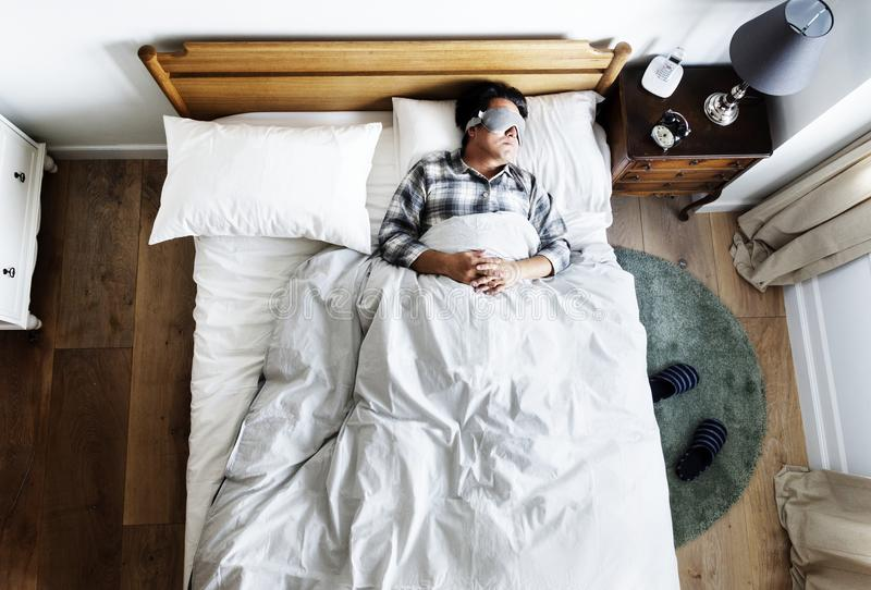 Японский человек спать на кровати с маской глаза стоковая фотография