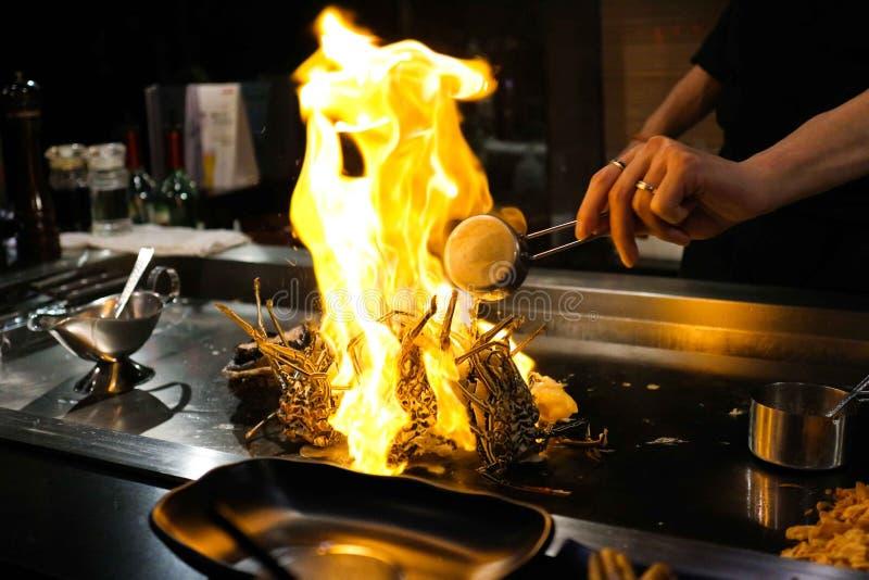 Японский шеф-повар варя омара на гриле теппаньяки с большим пламенем стоковое изображение