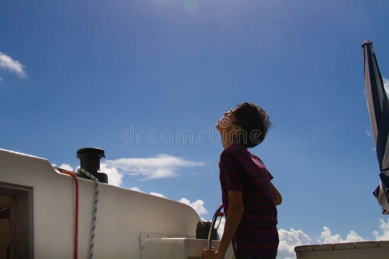 Японское рулевое колесо молодого человека на яхте стоковые изображения