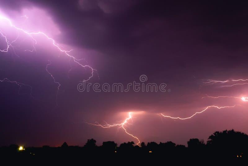 Яркая вспышка молнии осветила ночное небо и покрасила облака в голубом фиолетовом цвете стоковые изображения rf