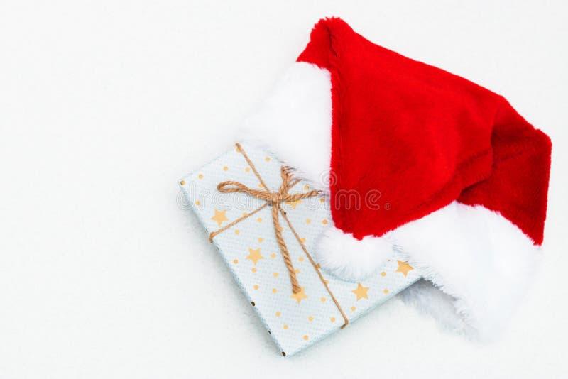 Яркая голубая подарочная коробка со звездами и красной шляпой Санта Клауса на белой предпосылке, подарке Нового Года стоковые фото